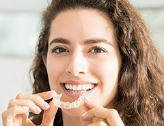 Woman holding Invisalign tray