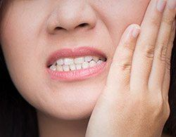 Closeup of person holding cheek in pain