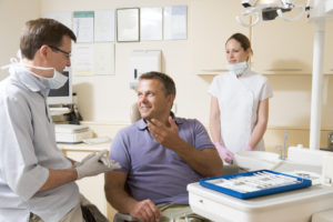 Man in dentla chair talking to dentist