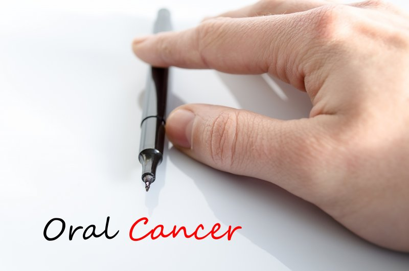 """a hand with a pen that's written """"Oral Cancer"""""""
