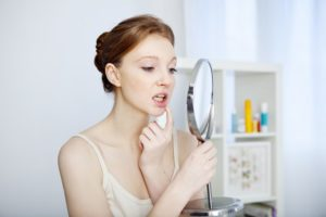 woman checking mouth in mirror for dental implant failure