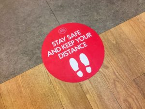 "red sign on floor that reads ""stay safe and keep your distance"""