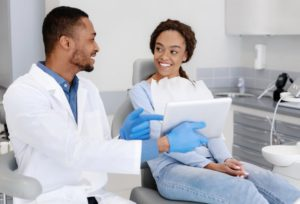 Woman smiles at her Newark dentist during dental checkup