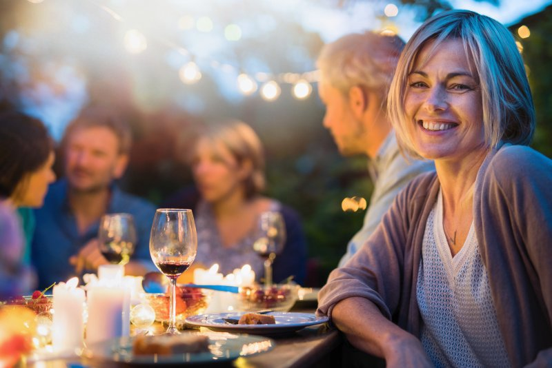 Woman with dental implants smiling at dinner table