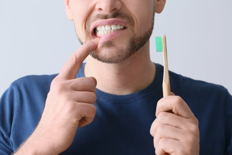 man holding toothbrush unhappily pointing at teeth